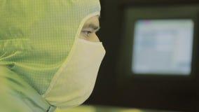 Scientifique d'ingénieur dans les costumes stériles, masque soyez dans un secteur propre, regardant un laboratoire d'usine-pilote banque de vidéos