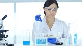 Scientifique dans des documents de lecture de laboratoire, écritures de résultat de recherche photo stock