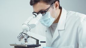 Scientifique dans l'uniforme regardant le microscope clips vidéos