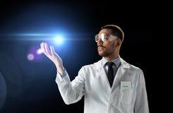 Scientifique dans le manteau de laboratoire et lunettes avec la lumière laser image stock