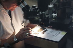 Scientifique de femme regardant par le microscope