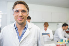 Scientifique de sourire avec des collègues au travail dans le laboratoire Image stock