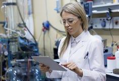 Scientifique féminin à l'aide de la tablette dans le laboratoire Images stock