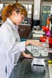 Scientifique féminin examinant la solution bouillie de produit chimique de becher Photo libre de droits