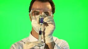 Scientifique injectant le liquide bleu dans la bouteille banque de vidéos