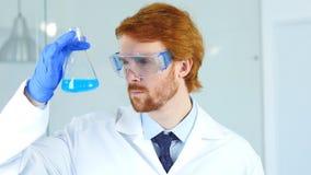 Scientifique, médecin Holding et regarder la solution bleue dans le flacon dans le laboratoire images libres de droits