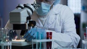 Scientifique médical mettant le verre avec le matériel biologique sur l'étape de microscope photographie stock libre de droits