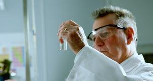 Scientifique masculin expérimentant dans le laboratoire 4k banque de vidéos