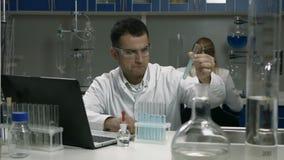 Scientifique masculin travaillant avec des tubes dans le laboratoire clips vidéos