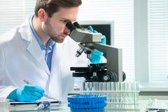 Scientifique regardant par un microscope photos libres de droits