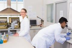 Scientifiques à l'aide du microscope Images libres de droits
