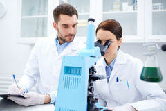 Scientifiques avec le presse-papiers et le microscope dans le laboratoire Photographie stock libre de droits