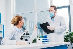 scientifiques dans des manteaux blancs et lunettes fonctionnant avec des réactifs et le microscope photo libre de droits