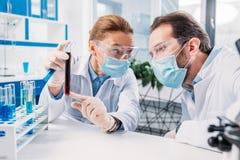 scientifiques dans les manteaux blancs et les masques médicaux fonctionnant avec des réactifs photo libre de droits