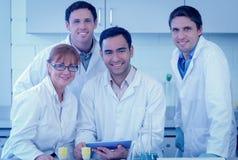Scientifiques de sourire avec la tablette dans le laboratoire Image libre de droits