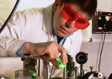 Scientist_1. The young scientist does experiences with a green beam of the laser in laboratory royalty free stock photos