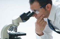 Scientist. A scientist looking through a microscope Royalty Free Stock Images