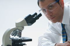 Scientist. A scientist looking through a microscope Stock Images