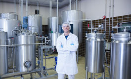 Scientist with arms crossed standing in front of container Stock Images