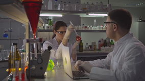 Scientist with assistant working in laboratory in the evening. Professional adult woman and handsome man carrying out experiments and analyzing their findings stock video footage