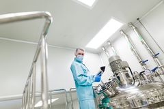 Scientist in checking the readings. Scientist in blue laboratory suit and gas mask stand in clean room and check graphs in tablet near big steel tank, chromed Stock Photos