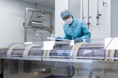Medical worker is making notes about serviceability of cebtrifug. Scientist in blue suit and with tablet behind the machine stock photo