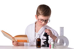 Scientist boy with a book in his hand look in mycrscope Stock Photos
