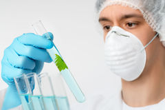 Scientist with brown eyes in protective wear with plant sample Stock Images