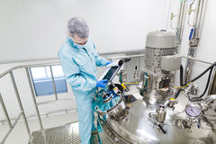 Scientist in checking the readings. Scientist in blue laboratory suit and gas mask stand in clean room and check graphs in tablet near big steel tank Stock Image