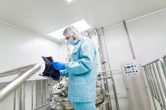 Scientist in checking the readings. Scientist in blue laboratory suit and gas mask stand in clean room and look at tablet Royalty Free Stock Photography