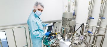 Scientist in checking the readings. Widescreen picture, scientist in blue laboratory suit and gas mask stand in clean room and check graphs in tablet near big Royalty Free Stock Images