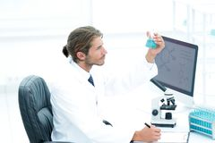 Scientist in the chemical lab examines a flask with a substance. A young man working in a scientific laboratory, collecting a flask Royalty Free Stock Photos