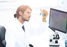 Scientist in the chemical lab examines a flask with a substance. A young man working in a scientific laboratory, collecting a flask Royalty Free Stock Image