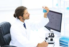 Scientist in the chemical lab examines a flask with a substance. A young man working in a scientific laboratory, collecting a flask Stock Photos