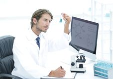 Scientist in the chemical lab examines a flask with a substance. A young man working in a scientific laboratory, collecting a flask Royalty Free Stock Images