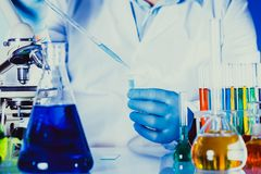Scientist in chemical lab. Scientist holds eppendorf tube and pipette. Focus on test tube stock image