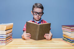 Scientist child reading book in the school library Royalty Free Stock Photos