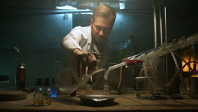 The scientist collects gas in the flask after the experiment. Strange scientist prepares a potion in the underground laboratory stock footage