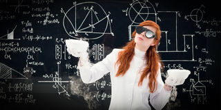 Scientist comparing two pots in chemistry lab. Young female scientist comparing two pots in front of a blackboard filled with chemical formulas in the chemistry royalty free stock image