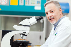 Scientist conducting research looking through microscope Royalty Free Stock Images