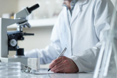 Scientist conducting research with microscope. Selective focus royalty free stock photo