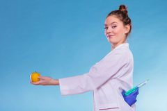 Scientist doctor with apple and syringe. GM Food. Royalty Free Stock Images