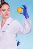 Scientist doctor with apple and syringe. GM Food. Stock Photo