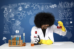 Scientist doing experiment with chemical liquid. Young scientist doing experiment with chemical liquid and doodle on interface screen Stock Photos