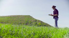 The scientist ecologist during the research. Woman standing on the meadow and writing something on the sheets of paper. The scientist ecologist during the stock footage