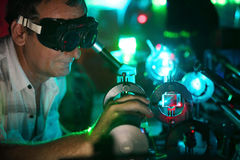 Scientist engaged in research in his lab. Scientist in laser vision glasses engaged in research in his lab show movement of microparticles by laser Royalty Free Stock Images