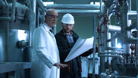 The scientist and engineer in plant. The doctor and the engineer looking at the blueprint in the factory. Horizontal indoors shot Royalty Free Stock Photography