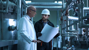 The scientist and engineer in plant. The doctor and the engineer looking at the blueprint in the factory. Horizontal indoors shot Stock Photography