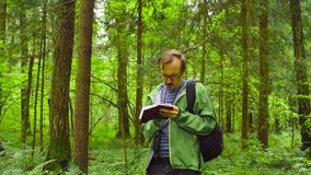 The ecologist in a forest writing in notebook. A scientist environmentalist exploring plants in a forest and writing data to a notebook stock footage
