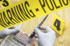 Scientist examines tests of cutting weapon of crime in a laboratory royalty free stock photography